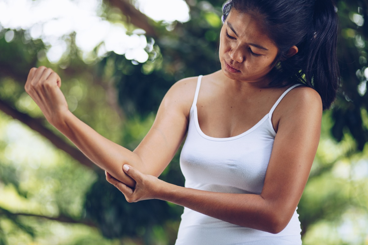 Woman holding her elbow examining pain