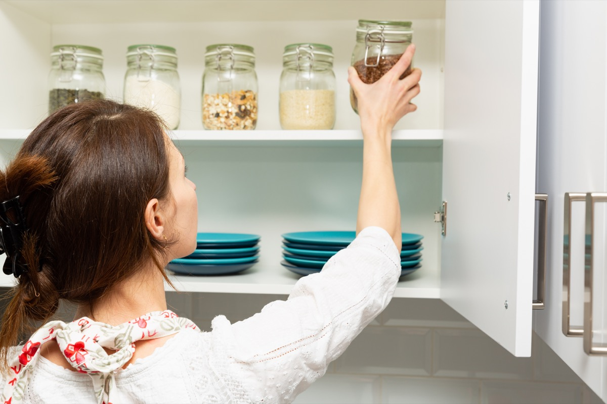 Woman putting away a jar in her organized kitchen cabinet