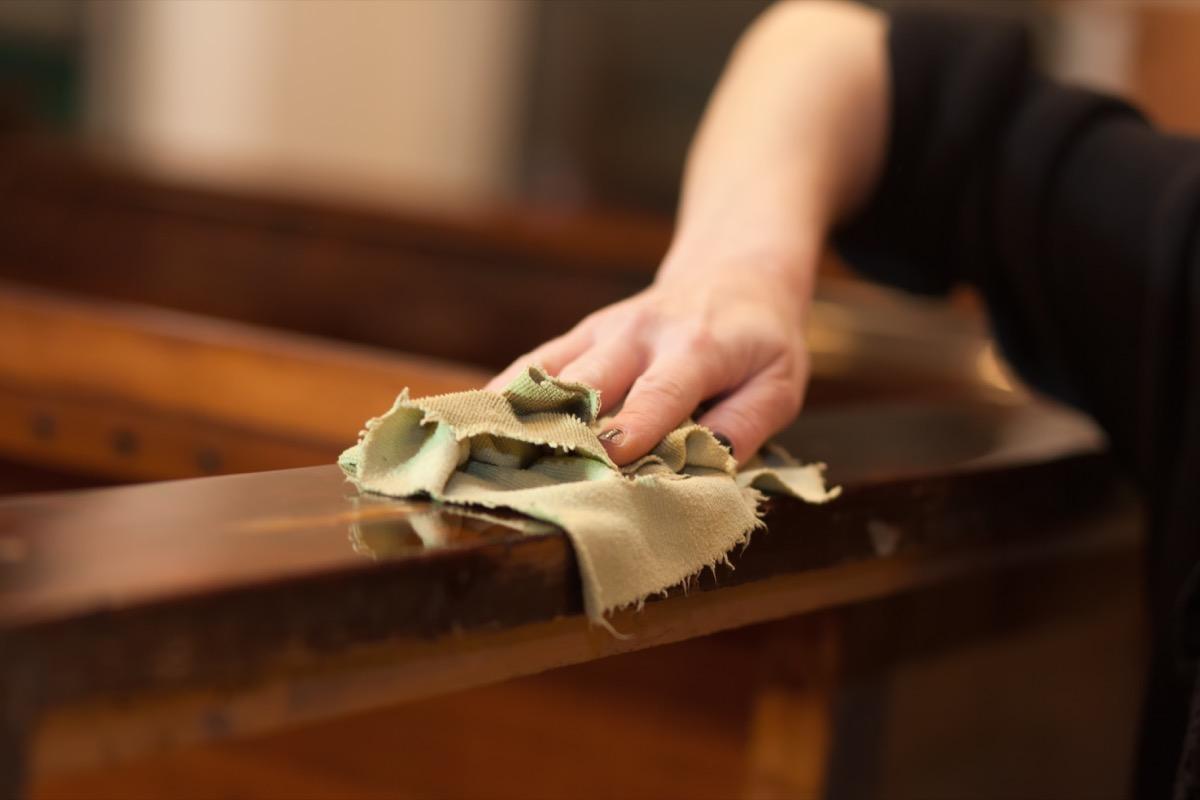 white hand polishing wood