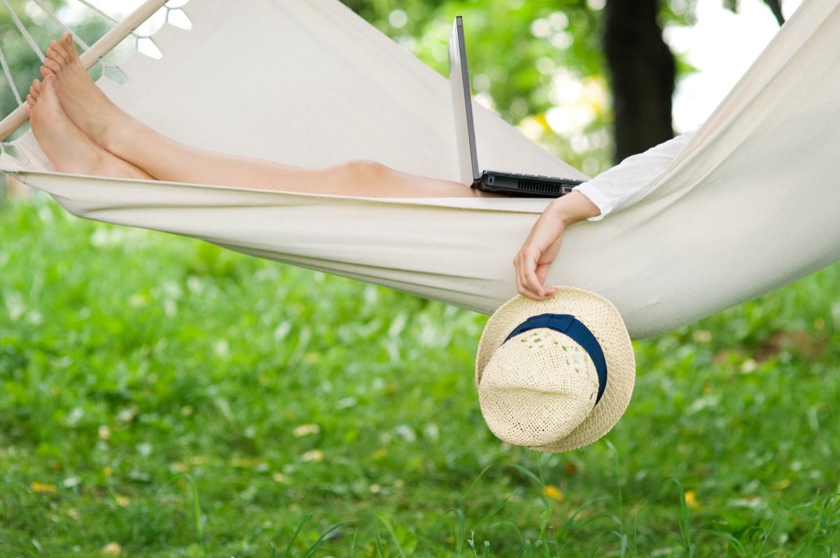 white woman relaxing outdoors in hammock with laptop