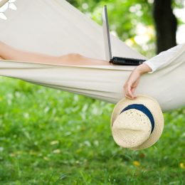 woman relaxing outdoors in hammock with laptop