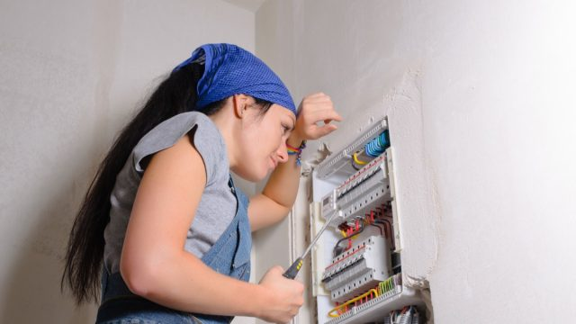 young white woman in bandana replacing electrical panel