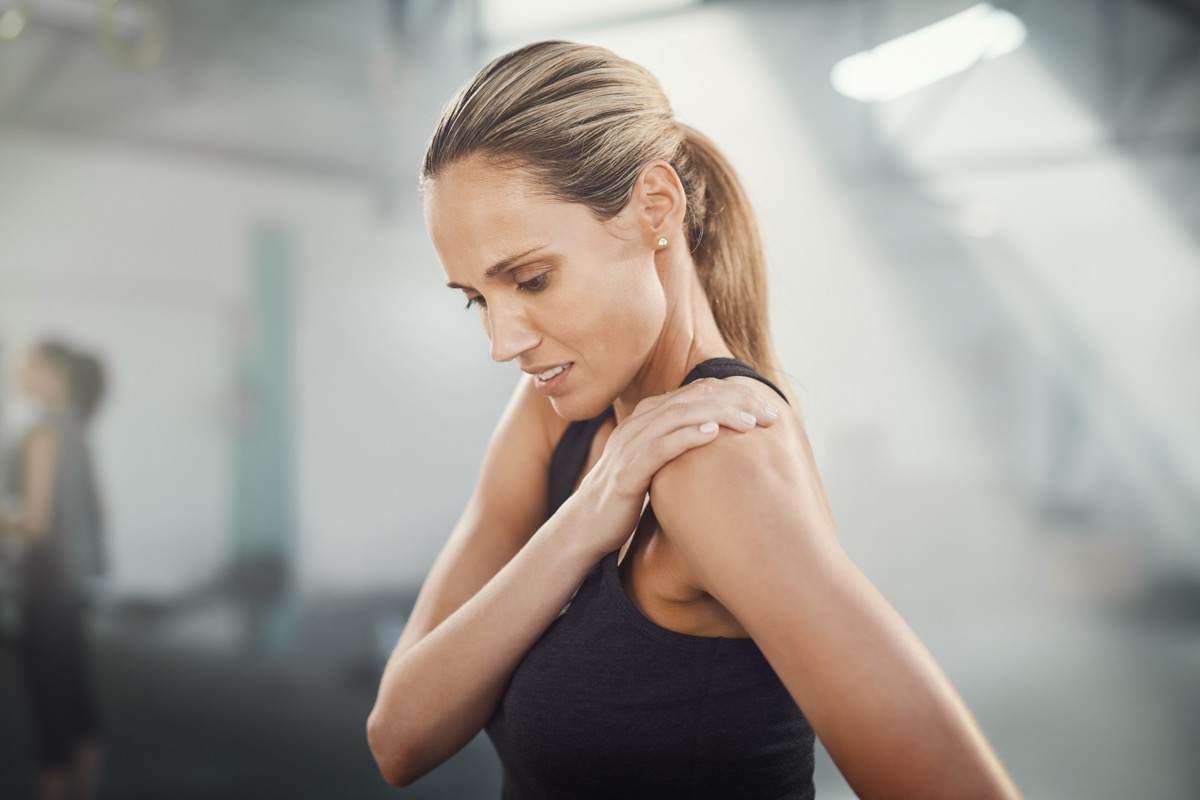 Sporty woman tending to shoulder injury tender joint