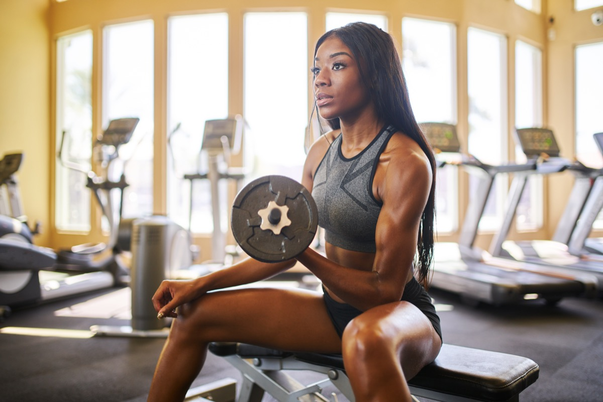 Woman sitting at the gym lifting a weight concentrating