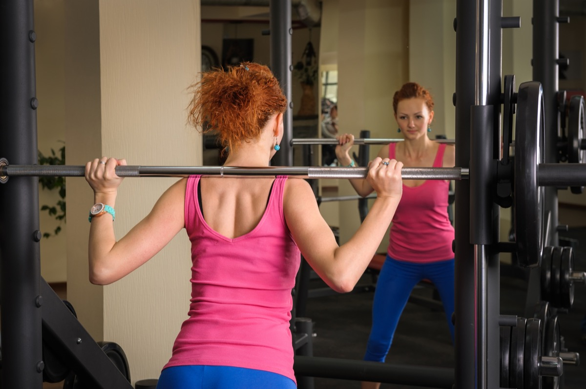 young red haired girl doing squats with barbell on smith machine in front of mirror