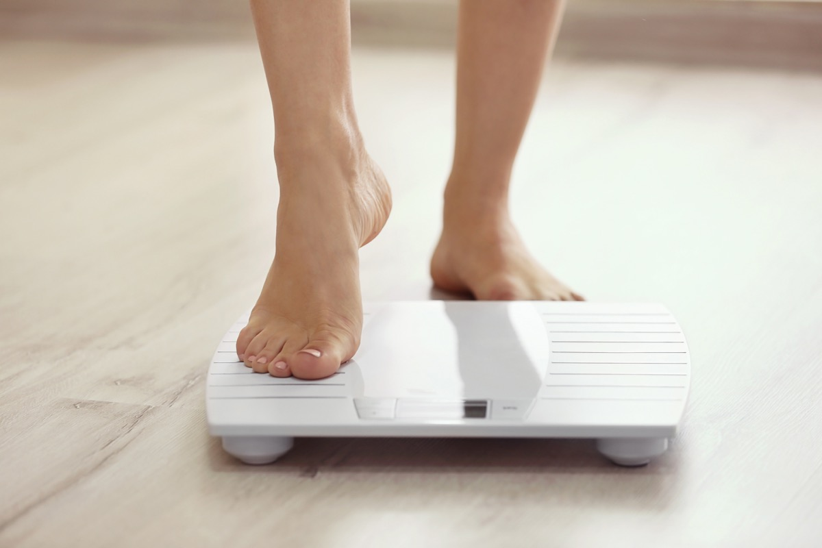 Woman stepping onto a scale to weigh herself