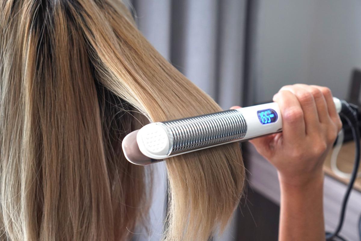 Woman using a hair straightener tool