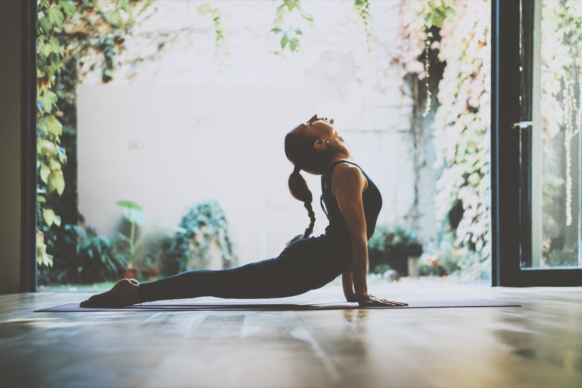 Woman stretching her back in cobra pose doing yoga