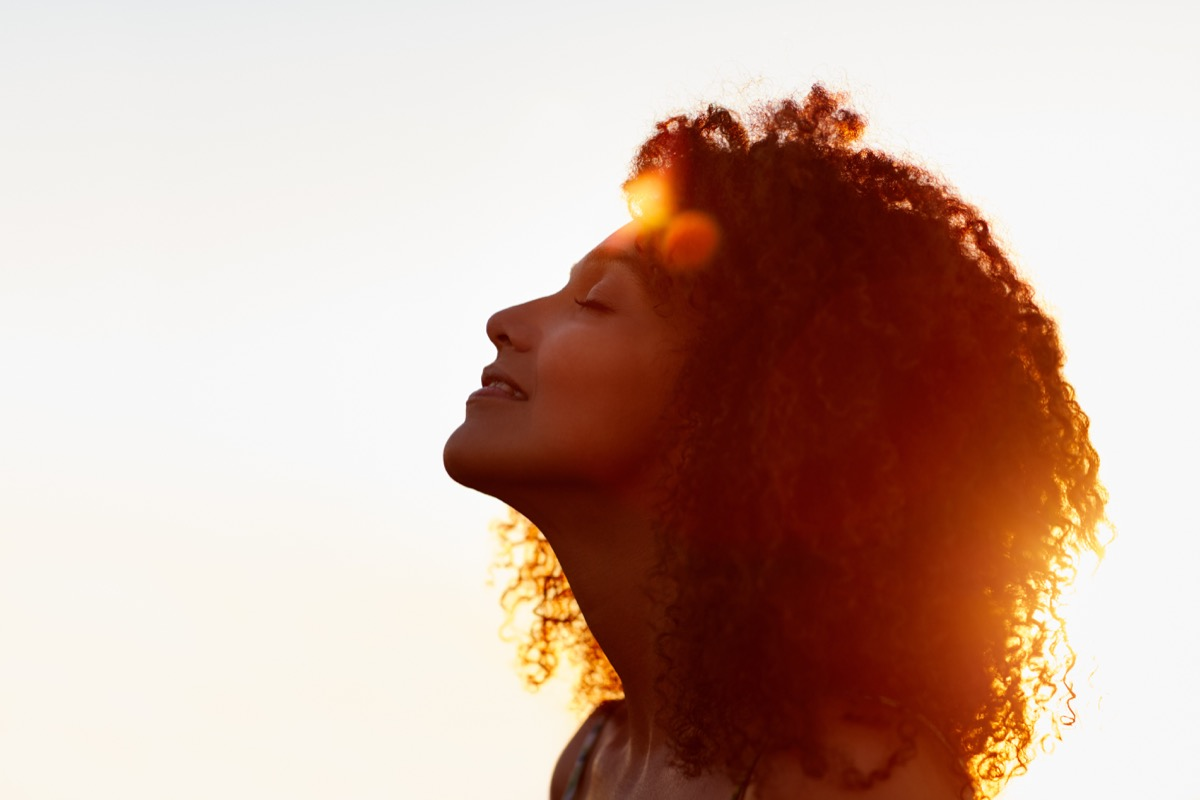 Woman smilling during a sunset taking in nature sounds