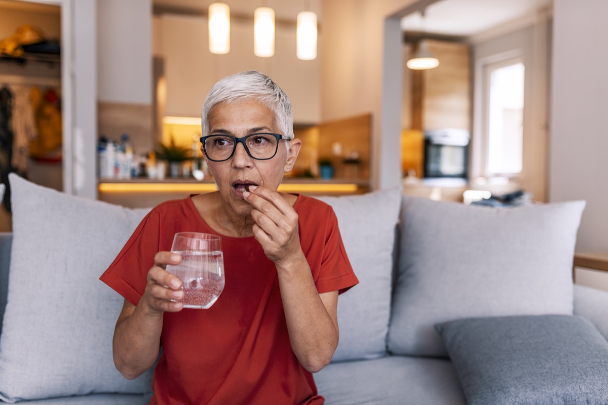 Mature woman's morning routine - holding medicine and water. Photo of Mature woman with pill and glass of water at home. Mature woman sitting on bed, suffering from depression. Woman takes pill with omega-3 and holding a glass of fresh water.