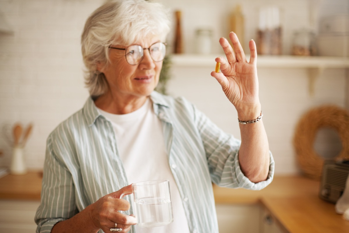 Woman taking a pill or a supplement