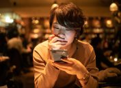 young woman using smart phone in cafe after work