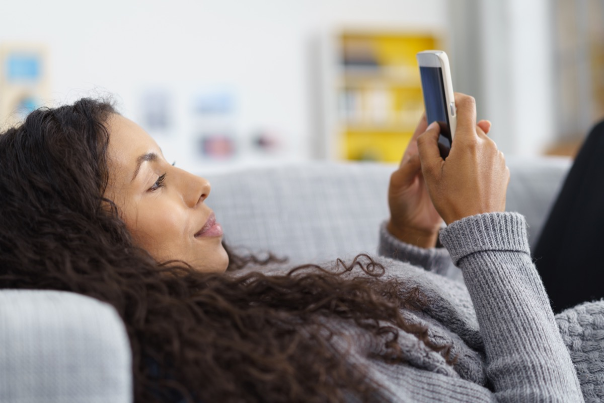 woman texting on a cell phone on the couch