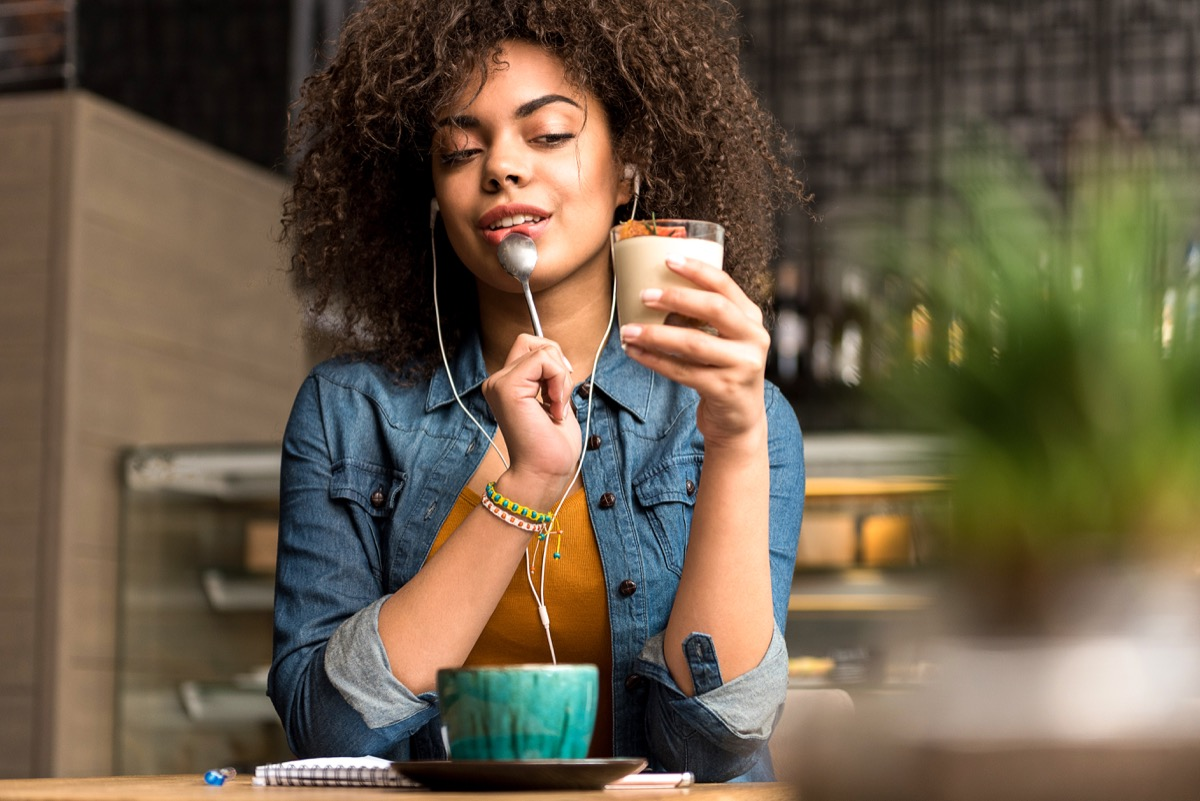 Woman listening to earphones while slowly eating a parfait in deep thought