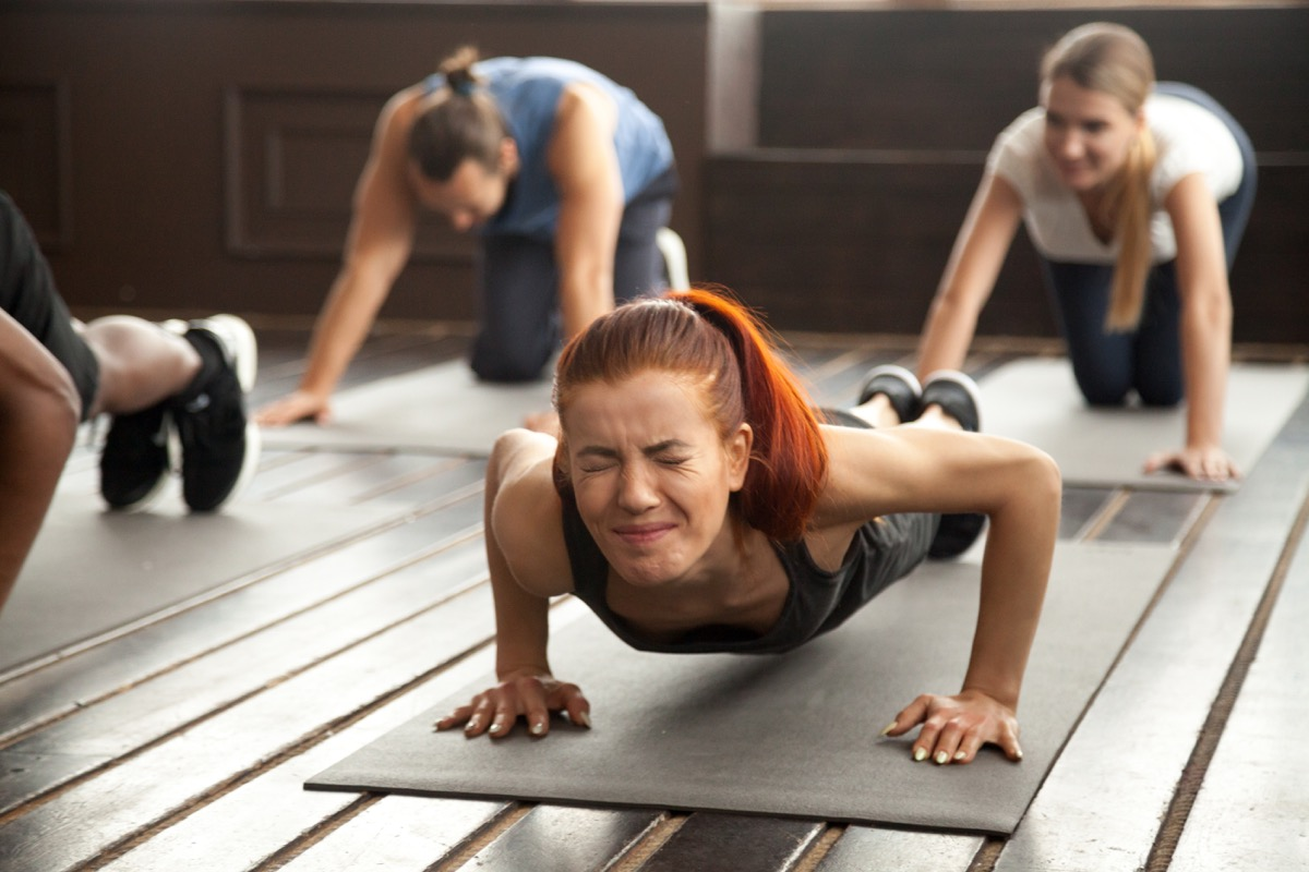Woman straining in a plank at the gym with an uncomfortable face
