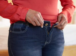 Woman trying to button her jean pants gained weight