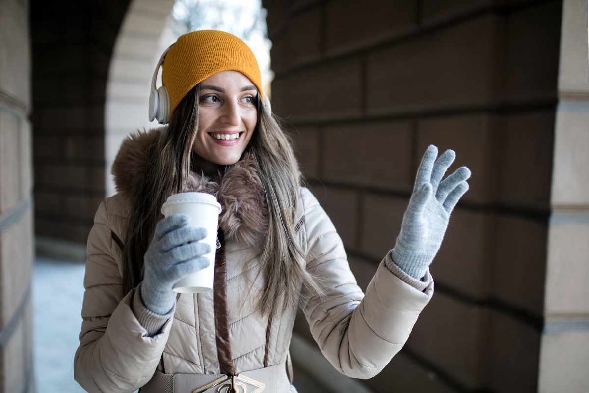 Young woman with coffee to go in winter outside waving