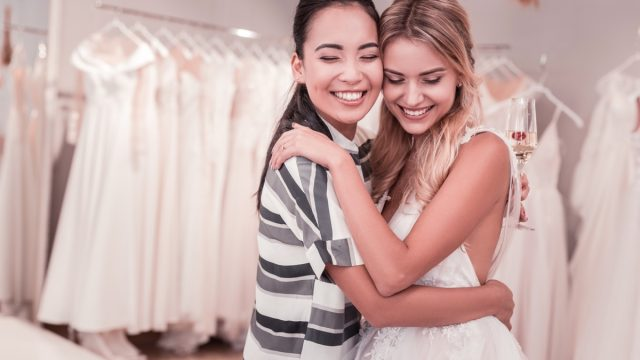 two women hugging in wedding gown and casual clothing at bridal shop