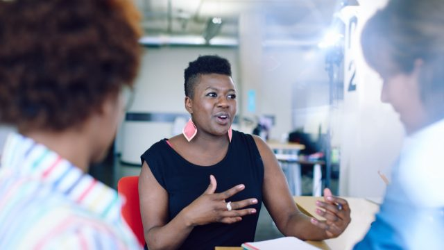 30-something female colleagues talking at work, black woman talking at work