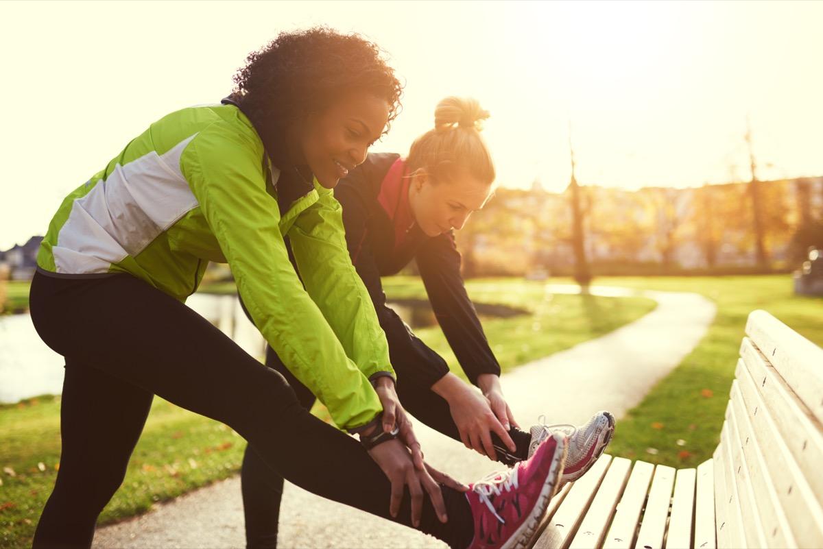 Women stretching before a run through a sunny park