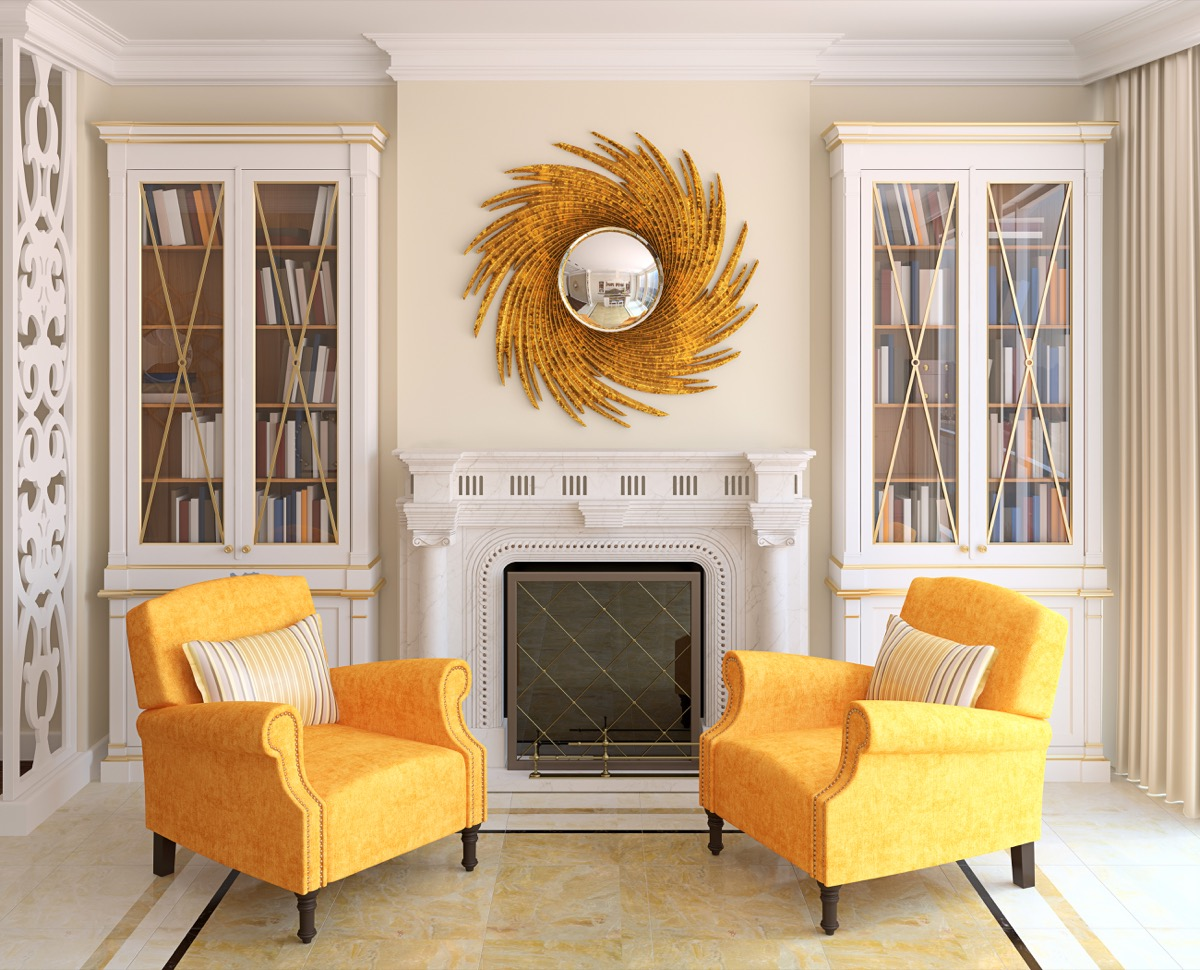 Yellow chairs and a sunburst mirror in a living room with a fireplace