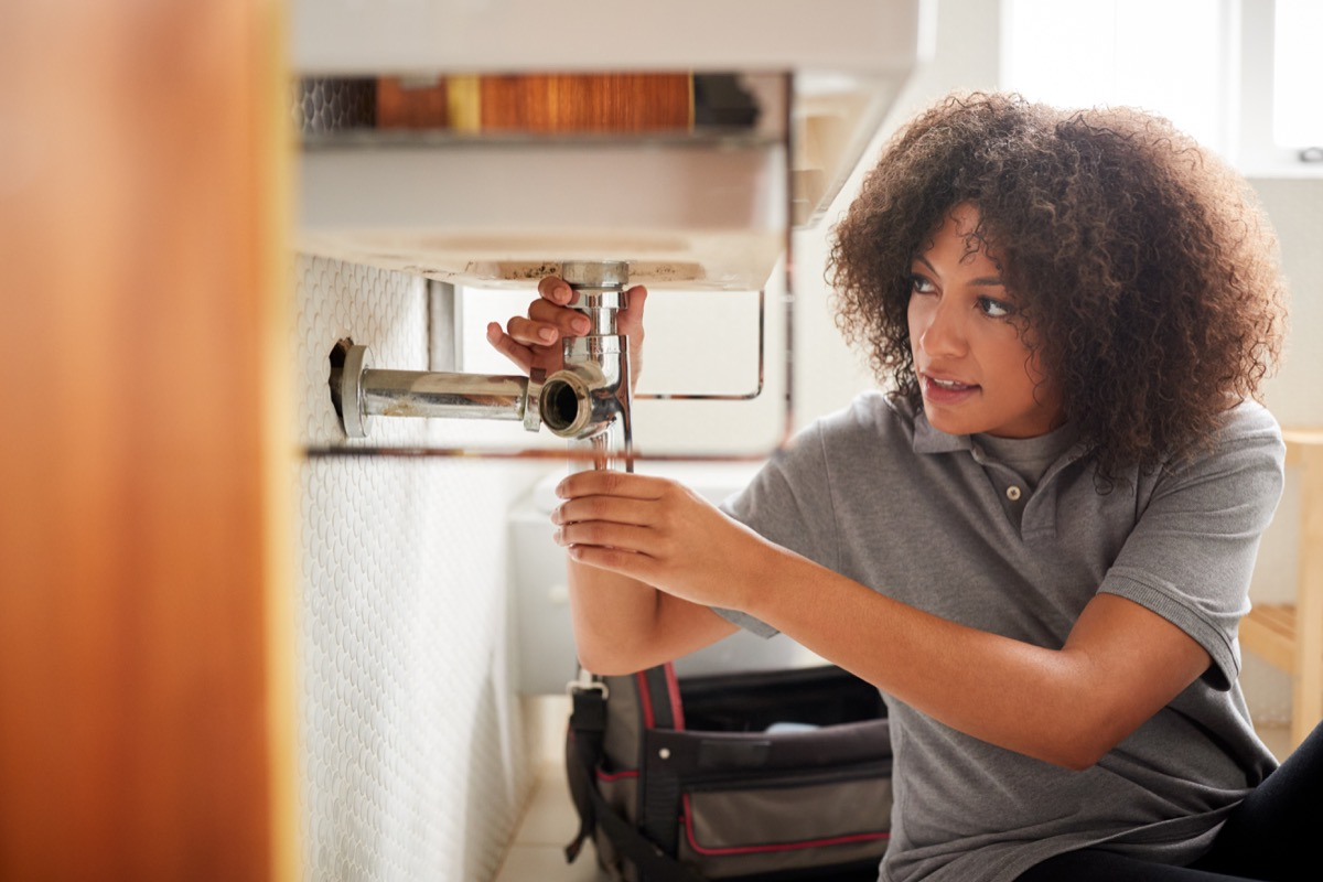 young black woman fixing sink