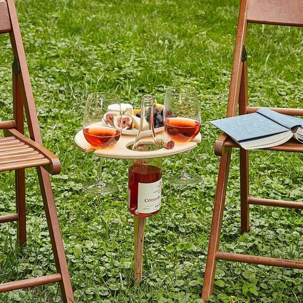 wine on wooden table and chairs on grass