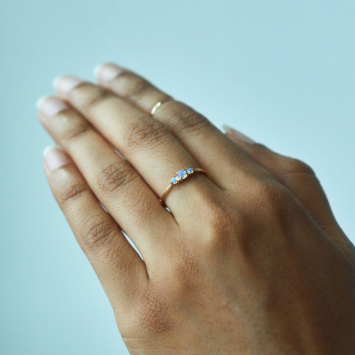 woman's hand wearing thin opal ring