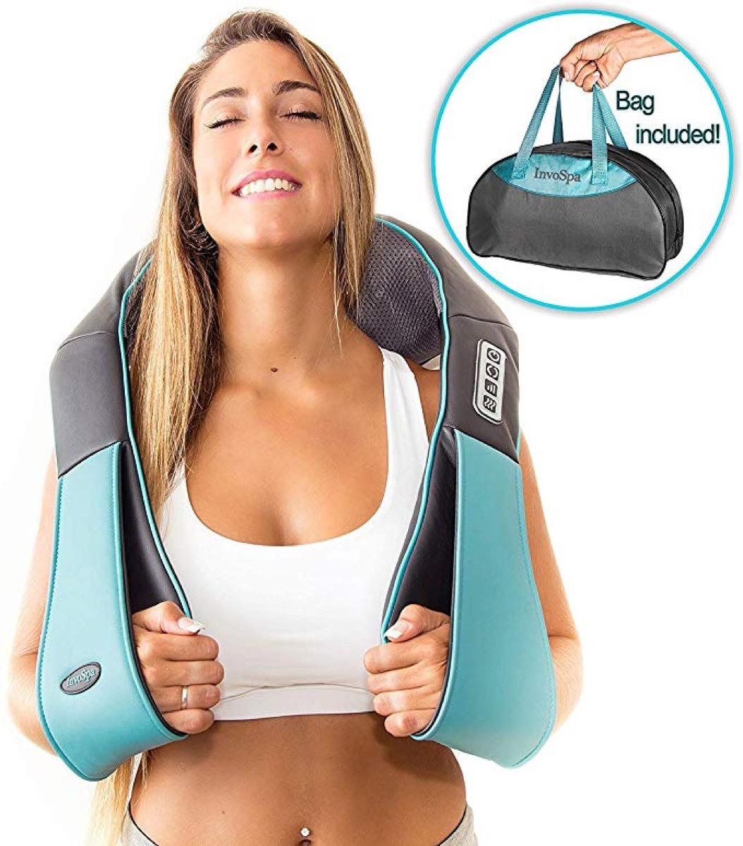 young blonde woman using back massager