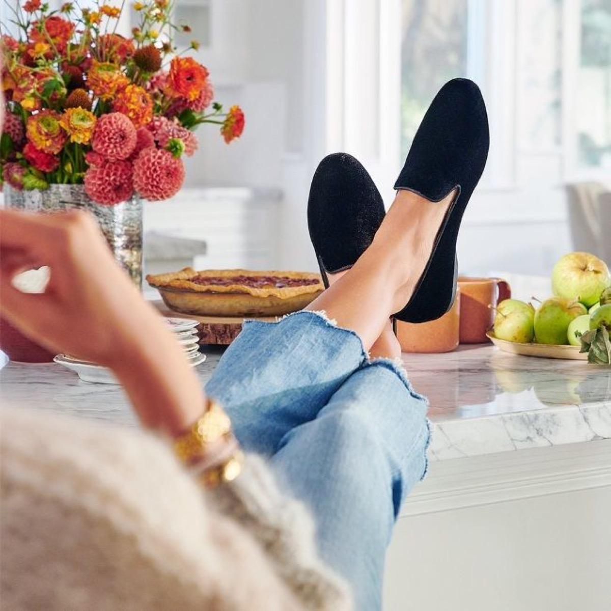 woman on couch wearing black velvet slippers