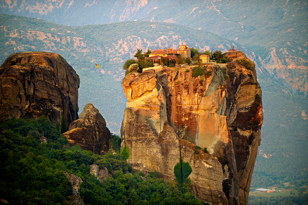 overview of the roussanou monastery on top of a giant rock formation
