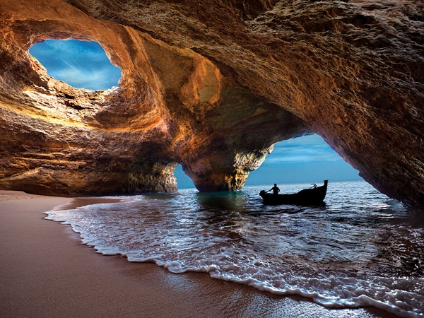 beach underneath a cave with a boat Portugal