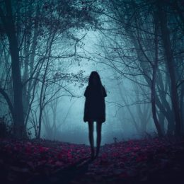 Scary ghost girl standing in the woods