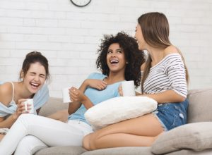 Three young women drinking coffee and laughing