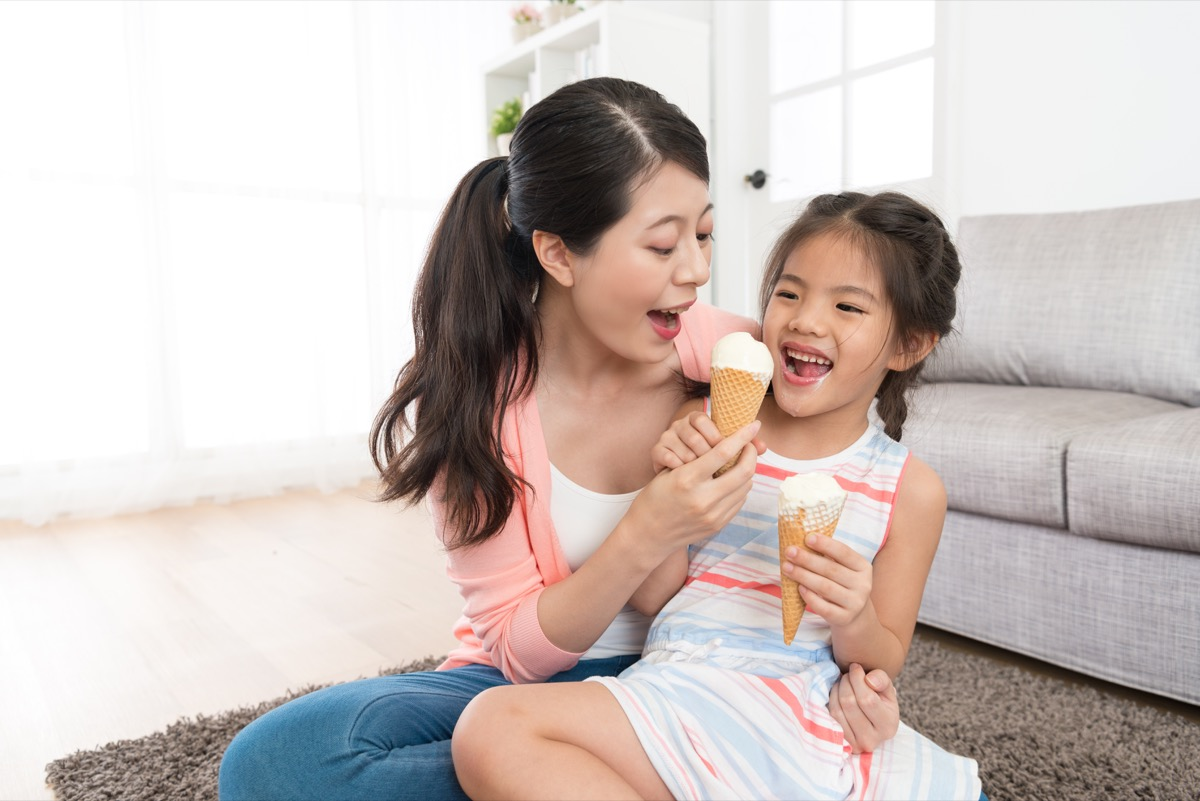 asian mom eating ice cream with young daughter