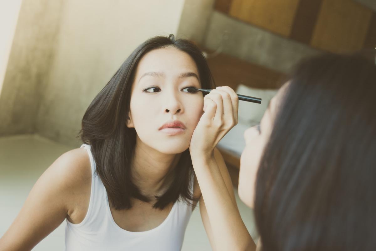 young asian woman putting on eye makeup