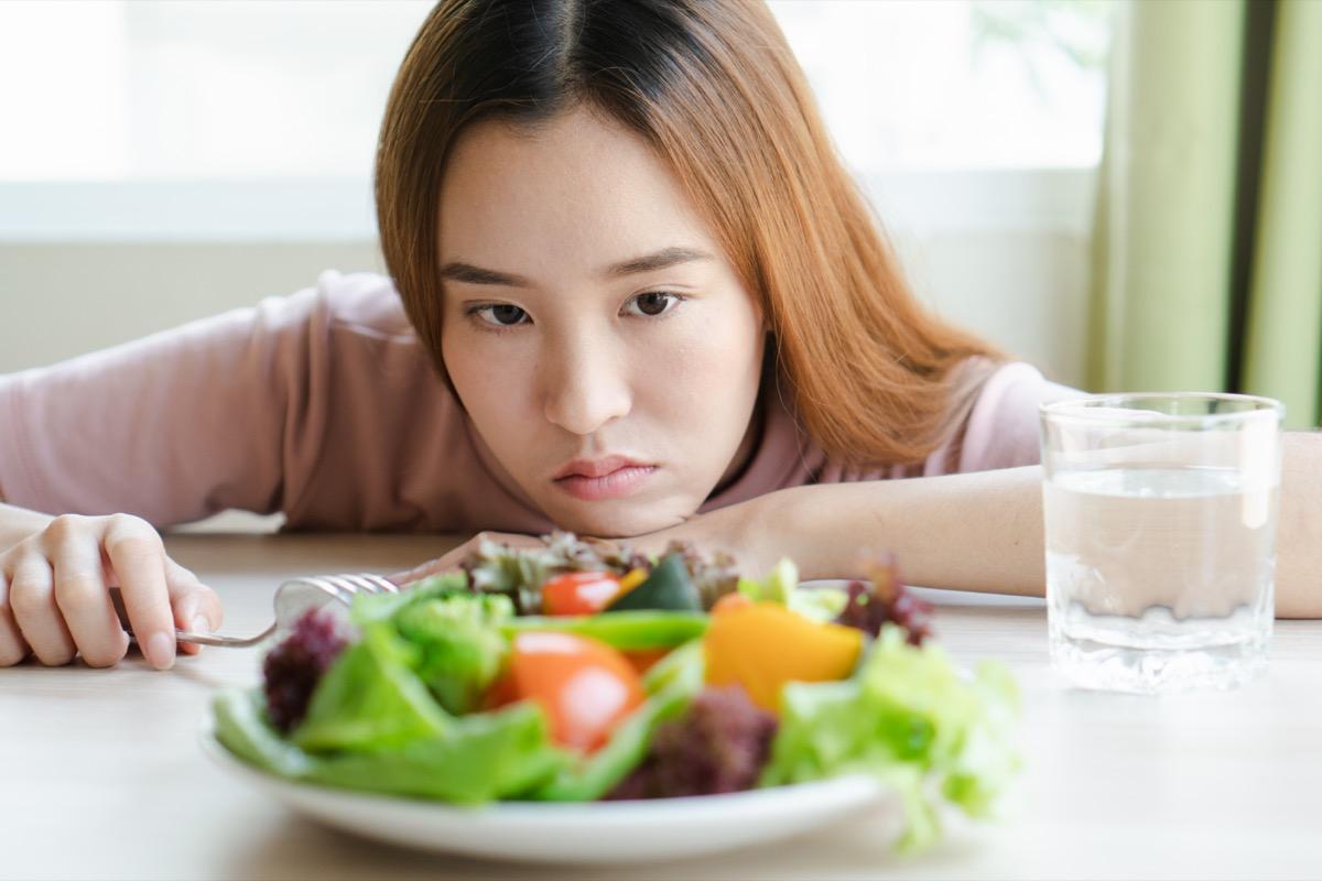 sad asian woman eating salad