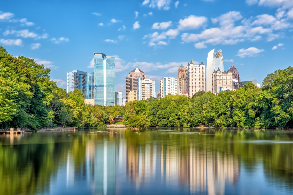 atlanta skyscrapers seen from a park with a body of water affordable vacations