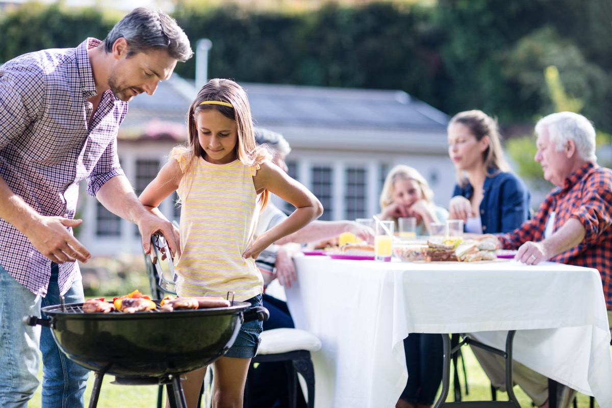 Dad barbecuing with daughter