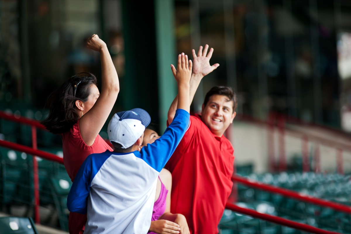 Dad high-fiving his son at a professional baseball game
