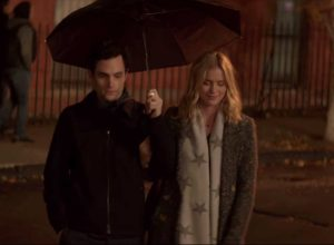 """elizabeth lail and penn badgley in still from """"you"""" holding umbrella and winter clothes"""
