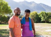 Cheerful black couple resting together after jogging in the park.