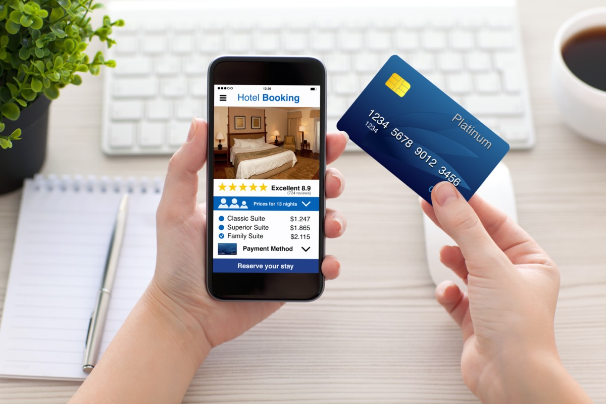 hands holding phone and credit card in the other