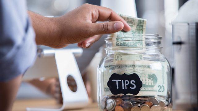 Unrecognizable male coffee shop customer places cash into a tip jar.