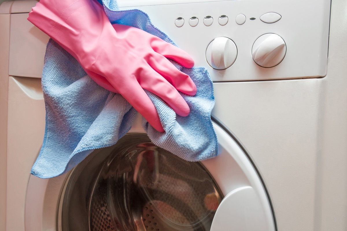 woman's hand with gloves cleaning exterior of washing machine