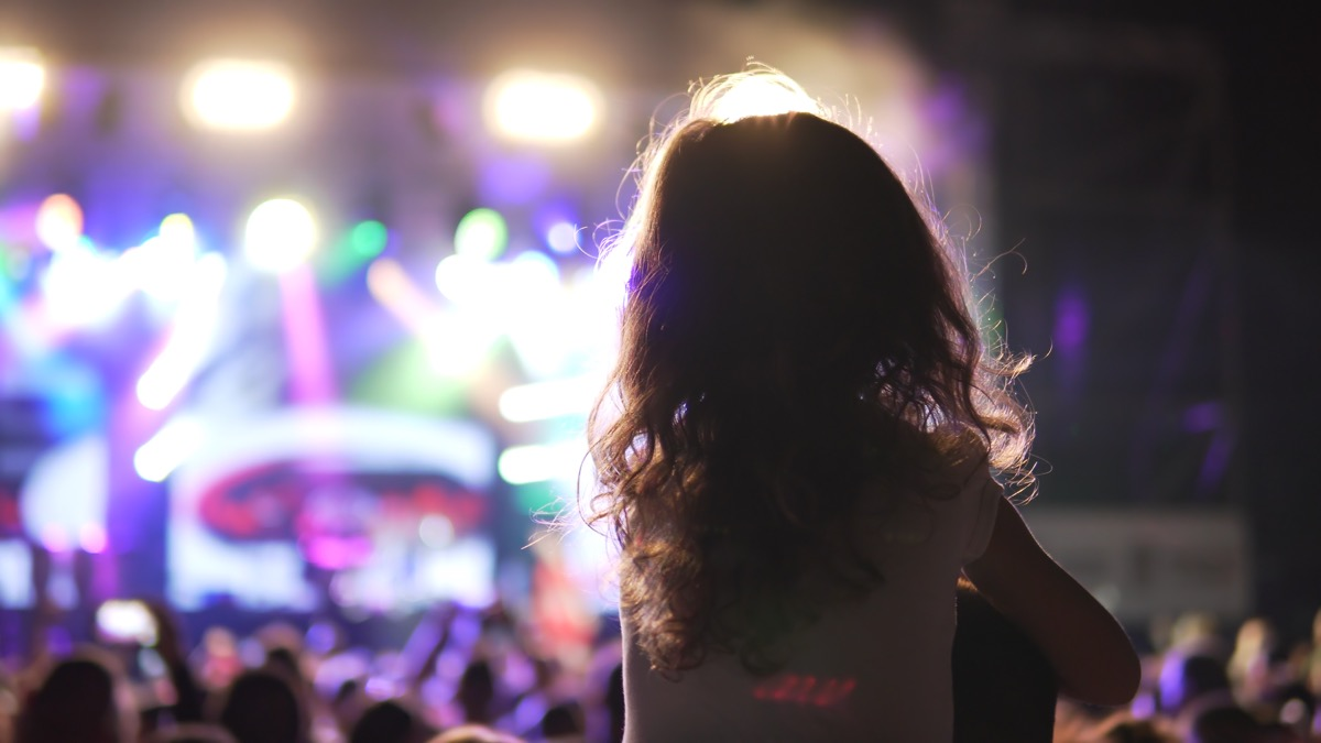 Little girl on shoulders watching a concert