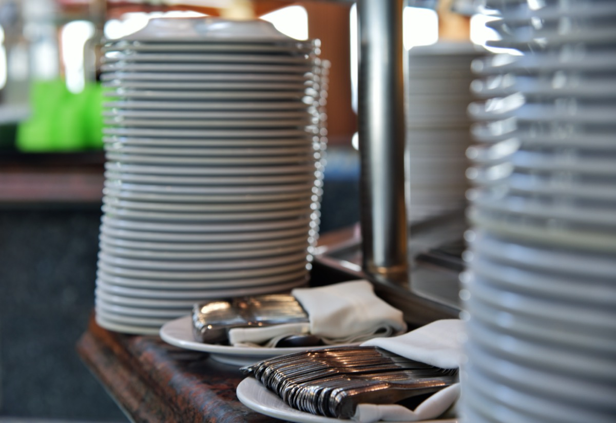 stacks of plates and silverware on a buffet