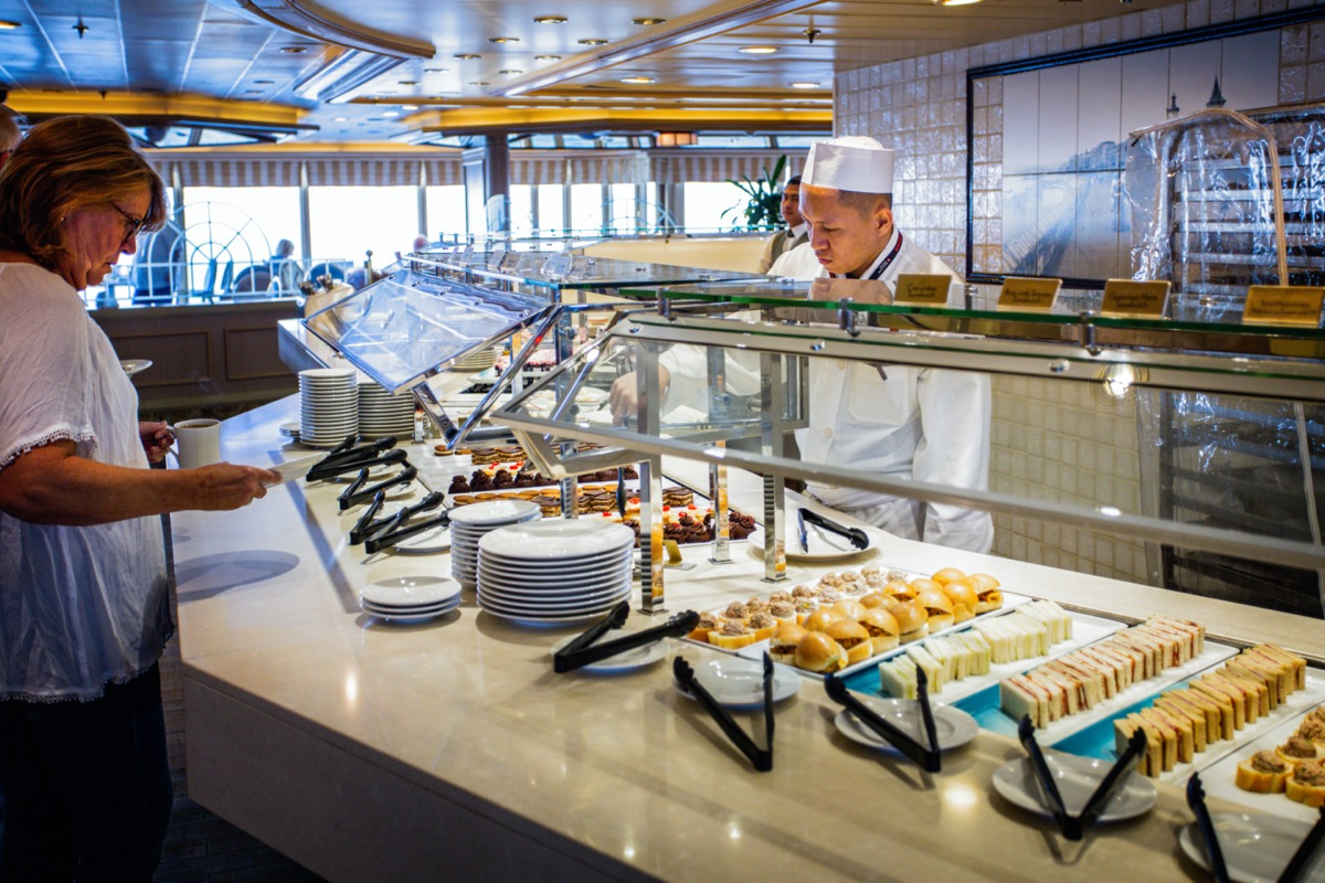 a woman puts food on her plate in a cruise ship buffet line