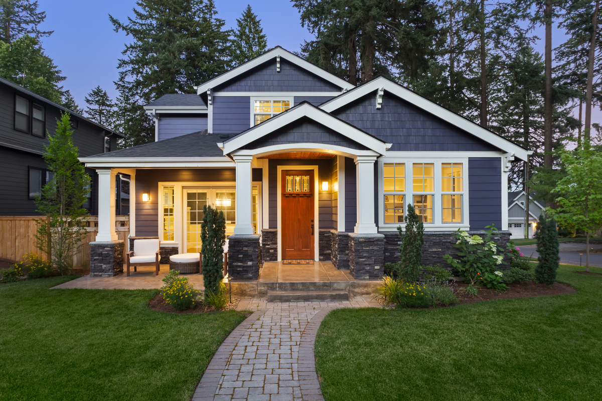 facade of dark blue home with manicured lawn, landscaping, and backdrop of trees