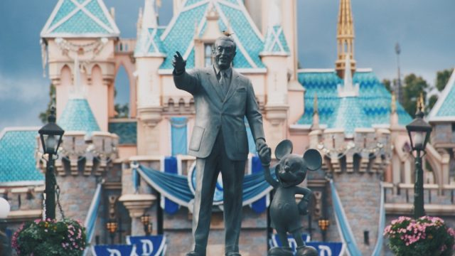 disney and mickey statue in front of disneyland